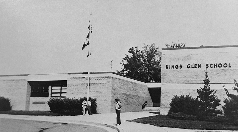 Kings Glen Elementary School Entrance, circa 1979, with safety patrol student standing on the sidwalk.