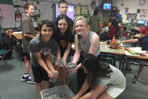 photo of students next to plastic bin of pop tabs