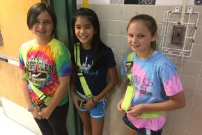 photo of three students with bus patrol belts on smiling