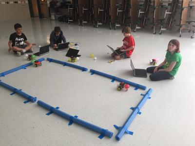 Photo of students racing balloons on robotic cars