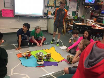 photo of students moving wagons on territory map of united states