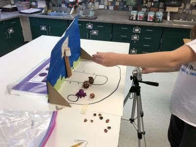 photo of student taking photos of a  mini painted set