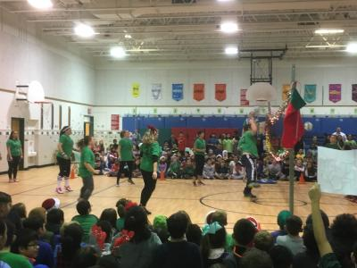photo of teachers playing volleyball against students in the gym with student body seated on floor watching and cheering