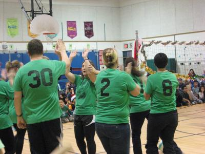 photo of teachers playing volleyball all wearing green tshirts