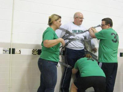Photo of teachers using duct tape to tape the principal to the wall