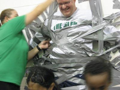 Photo of teachers and students using duct tape to tape the principal to the wall