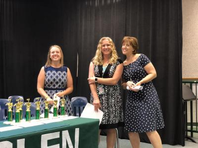 photo of three ladies standing next to a table of trophies
