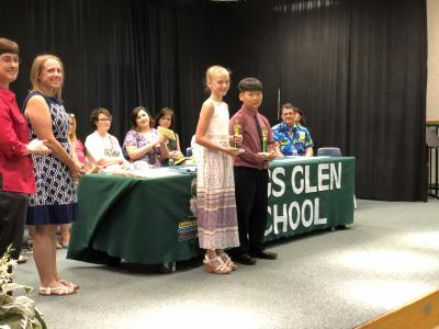 photo of students and teacher on stage next to table of trophies