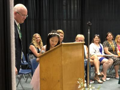 photo of student at podium on stage with adult supporting her
