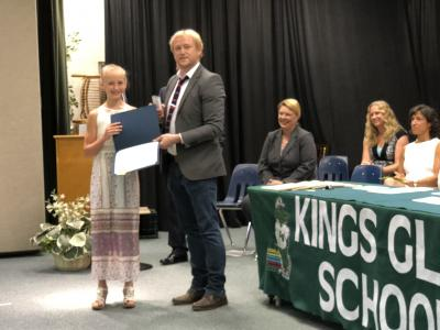 photo of student being congratulated by adult on a stage next to table with banner that reads kings glen school
