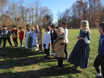 Photo of students standing outside and learning about colonial days