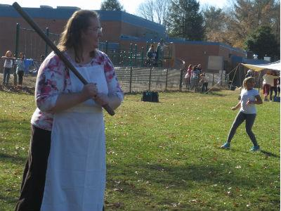photo of teacher outside in colonial garb playing colonial games