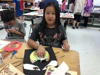 photo of student working with construction paper to create animal faces