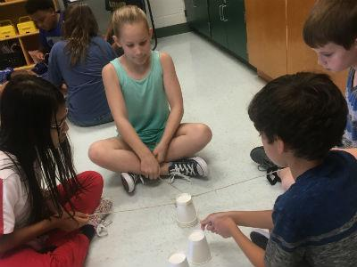 photo of students on floor with plastic cups and strings