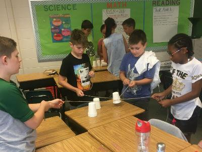 photo of students standing as a team with plastic cups and strings stacking cups