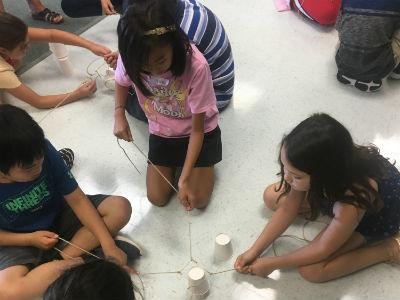 photo of students on floor with plastic cups and strings stacking cups